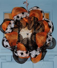 - Black and orange deco mesh on a wire wreath frame with sheer black and white spider ribbon, white yarn spider-webbed center, with black and orange spiders crawling all over it. - This spider wreath