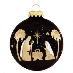 """The essence of Christmas is elegantly portrayed on this exclusive 3"""" glass ornament. Silhouettes of gold against a shiny black, star-filled background make this a favorite addition to your holiday décor.  Made in Hungary."""