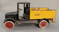 """Buddy """"L"""" Ice Delivery truck, classic 1920's model truck with black open cab and yellow bed covered with sliding cloth cover for bed.  ht. 12 in.; lg. 26 in.  Estimate: $400 - $800"""