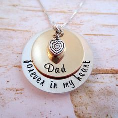 "This necklace is simple and classy and can be worn everyday. You can change ""Dad"" to any thing you'd like, as long as it fits. The bottom disc is 22 gauge Sterling Silver and measures 1"" and says, ""forever in my heart"". The top disc is a 22 gauge 3/4"" 14K Gold Filled disc that is personalized with your loved one's name. The sterling and gold discs have been slightly domed to add to it's elegance. This necklace is finished with small heart charm and is held together by a sterling silver 20""…"