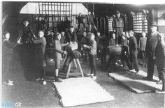 Gymnastiksalen Giersings Realskole   Små 30 drenge er i færd med redskabs  -gymnastik. Til højre i billedet ses  gymnastiklærer C.F. Hansen (1855-  1933). 1917-18