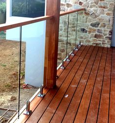 Glass Balustrades attached to timber decking with stainless steel spigots and timber handrail.