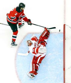 Split decision:   Jimmy Howard, right, of the Detroit Red Wings makes the save on John Moore of the New Jersey Devils on Dec. 11 in Newark, N.J. The Devils won 3-2 in overtime.  -    © Bruce Bennett/Getty Images