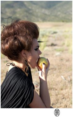High fashion photo shoot in the desert. Dramatic fashion photo shoot.  Mountain desert photo shoot with lots of drama.  Model with an apple.