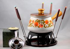 This is a vintage 1970s flower power mod style fondue set. The set comes in the original box and has 6 forks, the stand and bottom plate plus 2 burners or heating elements. It looks like ther...