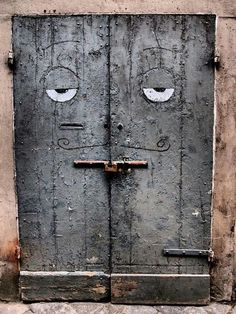 Old weathered gray doors with droll eyes, thin curled mustache and rod bar mouth