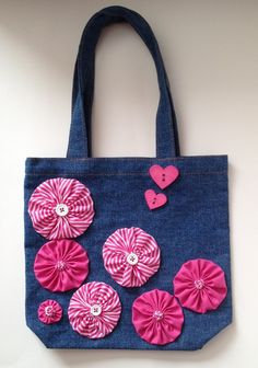 This whimsical denim tote features pink & striped hand sewn yo-yo flowers accented with teeny-tiny yo-yo & white button centers. It is also adorned with 2 cute heart-shaped novelty buttons, making it ideal for Valentines day gifting. The tote is cotto Denim Handbags, Denim Tote Bags, Diy Bags Purses, Denim Crafts, Jute Bags, Patchwork Bags, Wallets For Women, Bag Making, Hand Sewing
