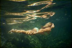 underwater in a mountain creek - A young woman swimming underwater in a small mountain creek in Northern California.