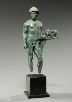 Etruscan bronze nude warrior holding a sacrificial hare. He wears a Negau helmet, a cloak over his left shoulder that wraps around his left forearm. On his extended left hand crouches a hare; a dagger in his right hand. Possibly Turms or Hermes. 4th century BC.