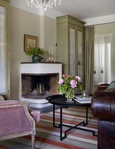 The fireplace is flanked by hand-made cabinets that have inspired color choice in the apartment. Table Swedish tin, velvet armchairs in Gustavian style, newly in Skåne. Rug from Garbo.