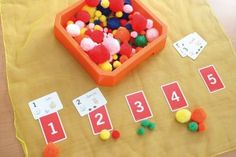 Coja cartas con números y un recipiente para meter diferentes numeraciones objetos (pompones, figurinas...). Coja el número que corresponda al número de la carta.