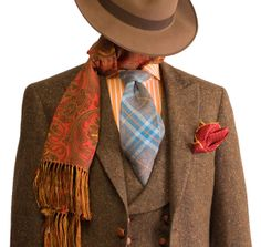 A sophisticated peak lapel, vested country suit featuring a shawl lapelled waistcoat in a handsome Donegal tweed and braided leather buttons by Adrian Jules. Harmoniously coordinated with shirt & accessories of autumnal colors.