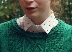 green cable knit sweater and dotted collared shirt.