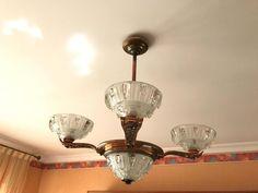 Lustre à monture cuivre à 4 branches et globes en verre moulé.
