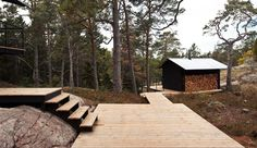 Cabin by Swedish studio Max Holst Arkitektkontor; Connecting wood boardwalk negotiating between changes in topography and defining separate zones
