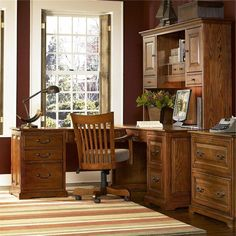 Classic Home Office Desk With Amazing Wooden Appearance Drawers Cabinet And Wooden Swivel Chair On Striped Patter Rug And Glass Window Including Dark Maroon Paint Wall Attractive Computer Desk Ideas for Stylish Home Office Decor Interior Design http://seekayem.com
