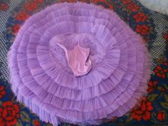 Another picture of tutu skirt. 3 Inch frills are sewn onto pants. Al 5 layers made from stiff gathered net frills are sewn onto  a one layer platter and give the tutu a slight bell or umbrella shape depending on the diameter of the hoop inserted.  The top two layers (tacked to the skirt) that lay flat on top can be made of gathered net, pleated or go very well with a ribbon candy overlay.