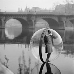 """American photographer Melvin Sokolsky shot these stunningly-surreal fashion photographs for Harper's Bazaar magazine in 1963. The """"Bubble Series"""" featured models in giant plastic bubbles, suspended above various locations (including the river Siene) in Paris."""