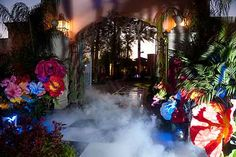 Alice in Wonderland theme gala decor... oversized tissue flowers. Bright pops of color against the spooky!