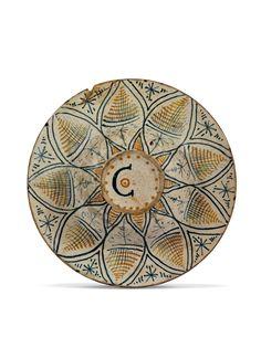 TONDINO  DERUTA, 1500-1520 CIRCA  Maiolica decorata in policromia con arancio, blu, verde rame e bruno di manganese nei toni del nero-marrone, su smalto bianco crema crettato.  Alt. cm 2,8, diam. cm 25, diam. piede cm 8,2.  Sigla sul retro Co.