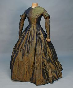CHANGEABLE SILK DAY DRESS, 1860's. Blue and gold taffeta having long collared sleeve, boned bodice with front hook & eye closures, full skirt with reverse pleats, side pocket, blue hem binding, bodice lined in brown cotton, skirt lined in polished natural cotton. B-32, W-22, L-52. (Two light stains on bodice, two minor holes near back hem, skirt lining some foxing).