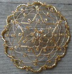 This womens kippah is crafted from gold colored wire and golden glass beads with and iridescent finish. Matching twisted glass bugle beads create a Star of David in the center. This elegant, versatile head covering has been an enduring favorite.  At approximately 5 in diameter with a clear comb attached, this light weight kippah is convenient and easy to wear. It arrives in an organza gift bag for safe keeping.  Keepsake Kippot have been carried in many synagogue gift shops and Judaica…