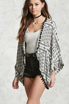 A woven kimono featuring an allover tribal-inspired print, an open front, a pom-pom trim, and cuffed kimono sleeves.