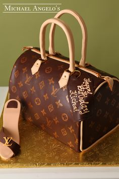 LV Speedy 30 & Shoe #14Handbag This is a replica of Louis Vuitton's Speedy 30 design. It is iced in monogrammed fondant and trimmed in cream. A Happy Birthday message is shown on the gift tag. This handbag is accompanied by a LV shoe handmade from gum paste.