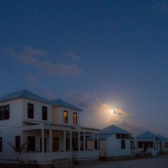 Ambergris Caye moonrise over Mahogany Bay Village with twin cottage windows glowing orange from the second level as the rest of the village street sleeps in Belize