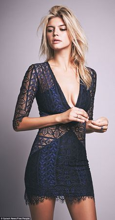 The model, 25, shows off her curves in a plunging navy and black lace dress with sheer panels