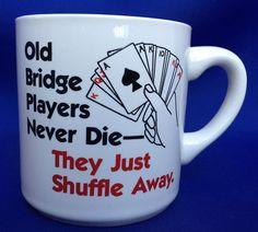 """Written on one side of the mug, """"Bridge Players Never Die They Just Shuffle Away"""". Manufacturer paint glaze bump on handle."""