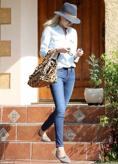 Rosie Huntington-Whiteley in a light denim button-down shirt, a pair of skinny indigo jeans, leopard print tote and a felt fedora