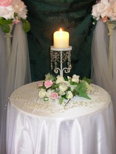 Unity Candle: A tall candle holder, flowers laid around the base, a lovely table cloth, and strings of decorative pearls for an elegant touch.