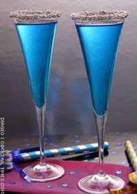 Midnight Kiss ~ 1 oz Smirnoff Vodka, 1/4 oz Blue Curacao, 1 tsp Lemon Juice, Champagne, Rimming: Gold Sugar