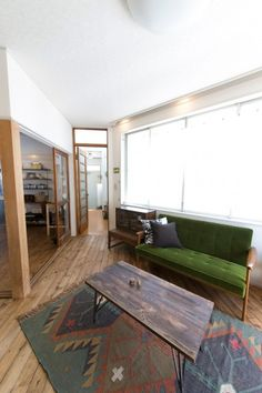 ソファーテーブルは、ダイニングテーブルのイメージに合わせて選択。グリーンのソファーはカリモク。