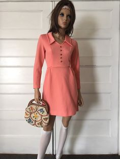 1970s vintage peach colored mini dress with a mod collar and gold buttons up the front. Long sleeves, empire waist with ties around the back and also zips up the back, big collar, very figure flattering. Rib knit polyester. Measurements: -Bust 35 -Waist 28 -Hips 38 -Length 33 -Sleeve length 21.5 -Shoulder seam to seam 14  Please see my shop for more retro 1970s clothing: https://www.etsy.com/shop/GypsysClosetVintage?ref=hdr_shop_menu  The vintage PURSE is here: https:...
