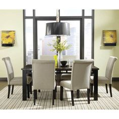 Use yellow artwork and a matching vase to bring out a neutral dining room set.