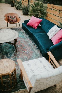 Rustic Bohemian Texas Winter Wedding at The Addison Grove | Mid-Century Modern Navy Velvet Sofa with African Mudcloth Upholstered Chairs, Round Leather Chairs, Rattan Wicker Accent Table, Mid-Century Coffee Table with an Engraved Brass Tray over an Antique Blue, Green, and Purple Persian Rug | via Birch & Brass Vintage Rentals for Weddings and Special Events in Austin, TX | Click to View More From This Wedding!