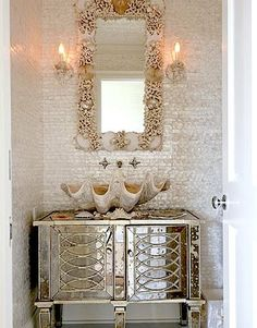 gorgeous shelled mirror and shell sink in beach bathroom. Also love the mother of pearl tiled wall and the mirrored vanity!
