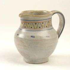 Carter, Stabler, Adams POOLE POTTERY  Earthenware jug thrown in buff body and covered with a matt grey glaze with yellow and blue geometric decoration.  11 cm high  Mark: Impress Carter Stabler & Adams, Poole England