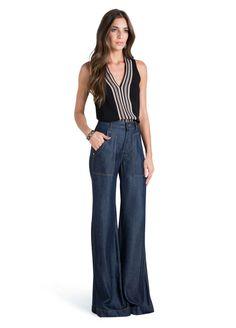 Calça pantalona, possui dois bolsos frontais com modelagem alongada e dois bolsos falsos embutidos na parte de trás, além de apresentar cós com passador para cinto e fechamento por