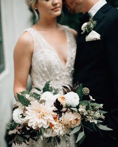 Beautiful bride on her wedding day wearing beaded v cut wedding gown holding beautiful pale toned bouquet