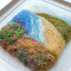 An original piece of textile art by Shropshire-based artist Maxine Smith. A one of a kind needle felted and hand embroidered picture inspired by the natural environment. This felted coastal scene has been created by hand using needle felting and hand embroidery to create a typical British seaside landscape. In the foreground sea thrift has been embroidered. The felted seascape is presented in a free standing white frame with mount. The approximate measurements are: Artwork: 3x2.75 inches…
