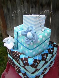 Square Diaper Cake! Usable items include:    Approx. 40 size 2 huggies diapers  1 plush 38x40 baby blanket  1 flannel receiving blanket  1 onesie (size 9