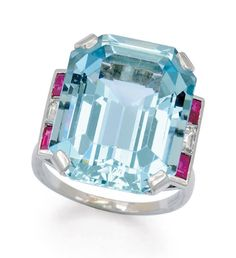 An Aquamarine, Ruby and Diamond Ring  Set with an emerald-cut aquamarine weighing approximately 22.00 carats, accented on either side by geometric channels of rubies and diamonds, mounted in platinum