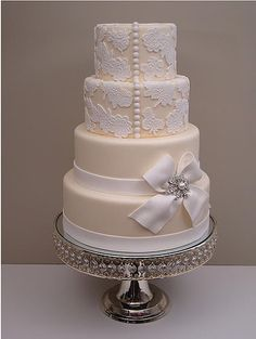 Ivory cake, white lace applique' and bow with brooch and ribbon