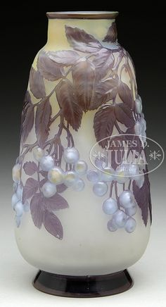 """Galle mold-blown vase has vine, leaves and berries descending from lip. Leaves are shaded green and blue when back lit, and appear lavender when unlit. Round berries are light blue, yellowish centers. Decoration is set against a frosted cream colored background, shading to pale yellow at top. Signed on side in cameo """"Galle"""". SIZE: 11-1/2"""" t. CONDITION: Very good to excellent. 49774-33"""