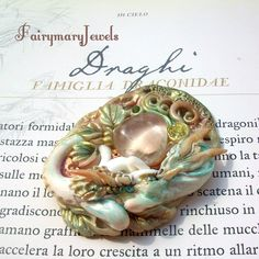 This was really a difficult challenge : the dragons are not easy to achieve and I was never fully satisfied with the results . For this dragon I was inspired by illustrations from the books Dragonology and Arthur Spiderwick . This dragon , guardian of a bright hyaline quartz , has been realized in polymer clay and swarovski . https://www.facebook.com/pages/Fairymary-Jewels/208528805873162?ref=hl