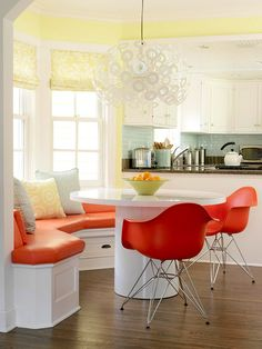 So much to love here: the bay window bench, the orange chairs, the pale yellow walls, the overhead lamp, and the breakfast room/kitchen combo