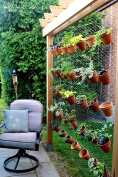 This vertical garden—built by affixing hex wire netting to a cedar frame—accommodates up to 35 small terra-cotta pots.
